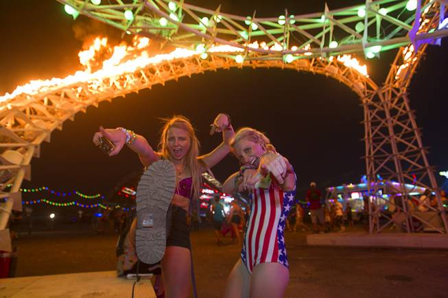 "Kylie Reagan, left, and Madi Lawton of Boulder, Colo. pose under ""Tympani,"" a sculpture by the Flaming Lotus Girls, during the final day of the 2014 Electric Daisy Carnival (EDC) at the Las Vegas Motor Speedway Sunday, June 22, 2014."