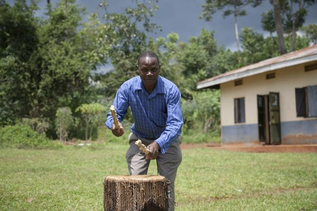 A community leader demonstrates an alert given to the community when a child is abducted using a large drum, in Kampala, Uganda. When a child goes missing, the villagers beat drums into a soaring rhythm that sends rescuers scampering through bushes. Others, riding motorcycles, try to block exit routes. With children being kidnapped and killed in ritual murders, a traumatized community here has created a rudimentary but potentially effective abduction alert system that has saved at least two children this year.