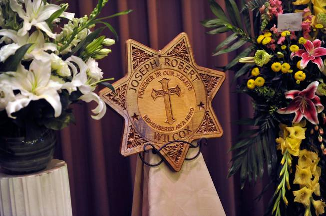 A wood-engraved placard for Joseph Wilcox is displayed during a memorial service at Palm Downtown Mortuary and Cemetery on Sunday, June 22, 2014. Wilcox, 31, was killed trying to stop Jerad and Amanda Miller in the midst of their shooting spree at an east valley Wal-Mart store June 8.