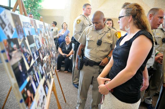 Las Vegas police and others look at a poster of photographs of Joseph Wilcox after a memorial service at Palm Downtown Mortuary and Cemetery on Sunday, June 22, 2014. Wilcox, 31, was killed trying to stop Jerad and Amanda Miller in the midst of their shooting spree at an east valley Walmart store on June 8.