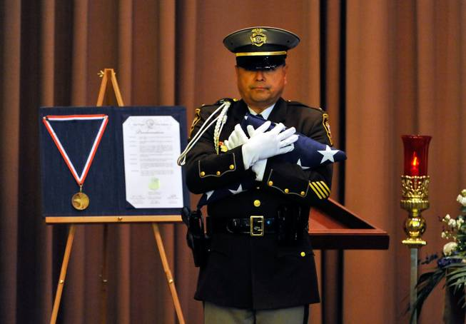 Las Vegas police Lt. Robert Smith of the honor guard presents an American flag during a memorial service for Joseph Wilcox at Palm Downtown Mortuary and Cemetery on Sunday, June 22, 2014. Wilcox, 31, was killed trying to stop Jerad and Amanda Miller in the midst of their shooting spree at an east valley Walmart store on June 8.
