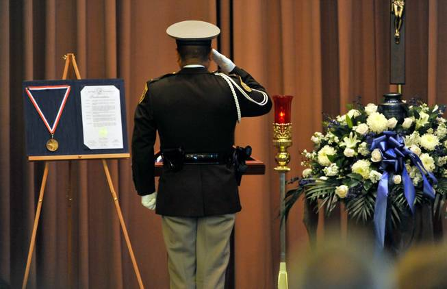 Las Vegas police Lt. Robert Smith of the honor guard salutes an American flag during a memorial service for Joseph Wilcox at Palm Downtown Mortuary and Cemetery on Sunday, June 22, 2014. Wilcox, 31, was killed trying to stop Jerad and Amanda Miller in the midst of their shooting spree at an east valley Walmart store on June 8.