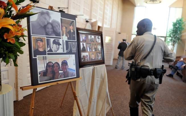 A Las Vegas police officer looks at a poster of photographs of Joseph Wilcox before a memorial service at Palm Downtown Mortuary and Cemetery on Sunday, June 22, 2014. Wilcox, 31, was killed trying to stop Jerad and Amanda Miller in the midst of their shooting spree at an east valley Walmart store on June 8.