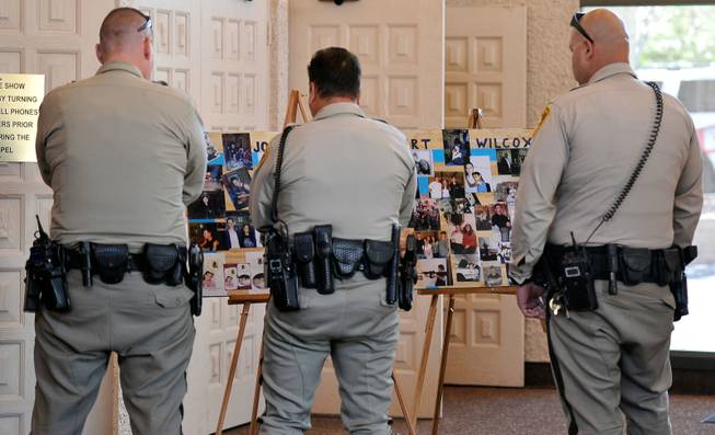 Las Vegas police officers look at a poster of photographs of Joseph Wilcox before a memorial service at Palm Downtown Mortuary and Cemetery on Sunday, June 22, 2014. Wilcox, 31, was killed trying to stop Jerad and Amanda Miller in the midst of their shooting spree at an east valley Walmart store on June 8.