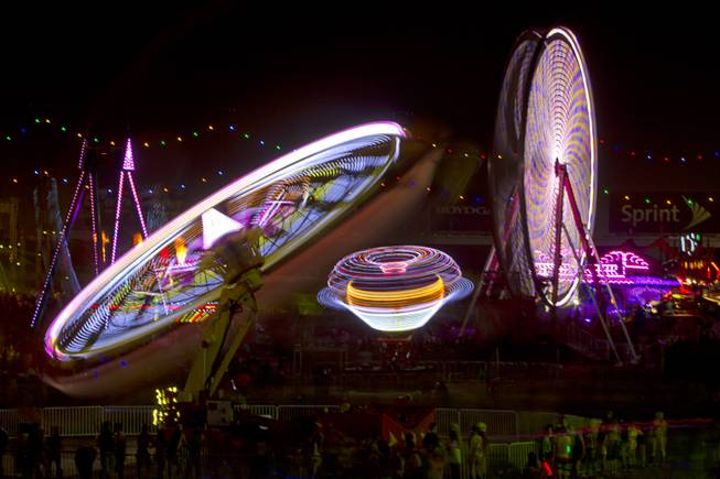 Carnival rides spin during the final night of the 2014 Electric Daisy Carnival (EDC) at the Las Vegas Motor Speedway Sunday, June 22, 2014.