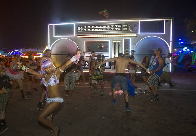 Attendees dance in front of a mock-up of a giant boom box during the final night of the 2014 Electric Daisy Carnival (EDC) at the Las Vegas Motor Speedway Sunday, June 22, 2014.