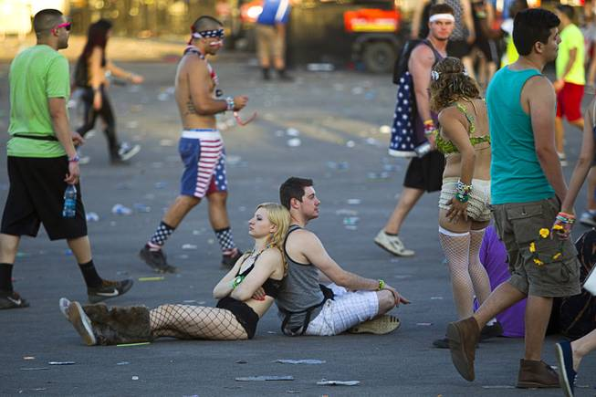 A pair of fans rest against each other before leaving the Las Vegas Motor Speedway after the final night of the 2014 Electric Daisy Carnival (EDC) Sunday, June 22, 2014.