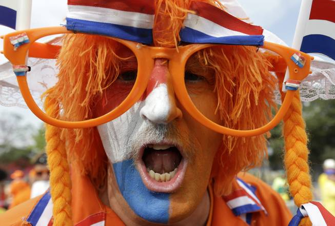 A Dutch fan cheers for his national team before the group B World Cup soccer match between the Netherlands and Chile at the Itaquerao Stadium in Sao Paulo, Brazil, Monday, June 23, 2014.