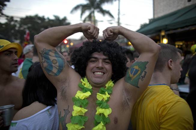 A fan shows off his muscles sporting tattoos of national flags from Brazil and Argentina, as thousands watch the World Cup group A match between Brazil and Cameroon, in the Vila  Madalena neighborhood, in Sao Paulo, Brazil, Monday, June 23, 2014. Brazil won 4-1. (AP Photo/Dario Lopez-Mills)
