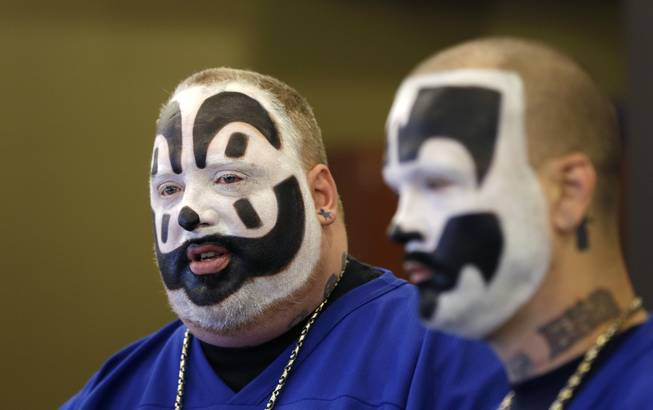 In this Jan. 8, 2014, photo, Joseph Bruce, aka Violent J, left, and Joseph Utsler, aka Shaggy 2 Dope, members of the Insane Clown Posse, address the media in Detroit. The U.S. Justice Department is asking a judge to dismiss a lawsuit by Insane Clown Posse, which objects to a report that describes its fans as a dangerous gang.