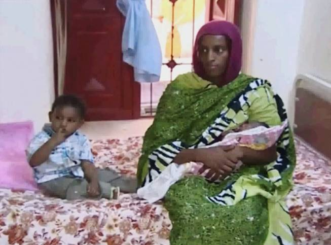 In this file image made from an undated video provided Thursday, June 5, 2014, by Al Fajer, a Sudanese nongovernmental organization, Meriam Ibrahim, sitting next to Martin, her 18-month-old son, holds her newborn baby girl that she gave birth to in jail last week, as the NGO visits her in a room at a prison in Khartoum, Sudan. Sudan's official news agency, SUNA, said the Court of Cassation in Khartoum on Monday, June 23, canceled the death sentence against 27-year-old Meriam Ibrahim after defense lawyers presented their case. The court ordered her release.