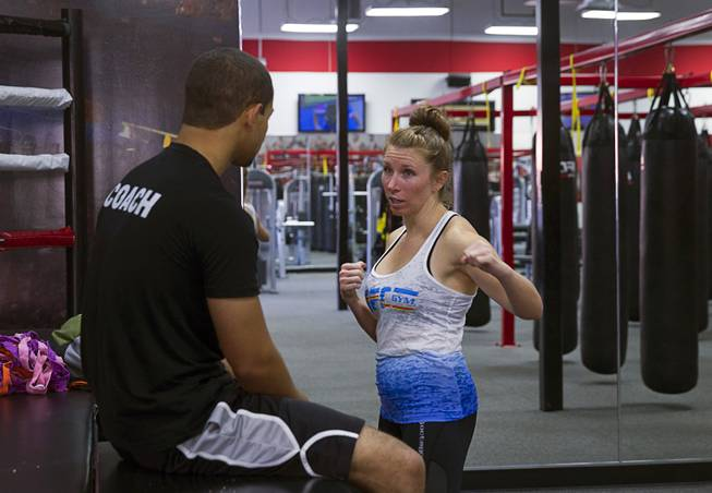 Rushelle Kiesel talks with instructor Seth Shaffer after a boxing group class at the UFC Gym at 4360 Blue Diamond Rd. Tuesday, June 24, 2014.