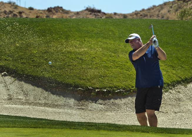 Gary Schade wedges a ball from the sand as HELP of Southern Nevada hosts its 20th Annual Golfers Roundup at Cascata Golf Course in Boulder City on Tuesday, June 24, 2014.