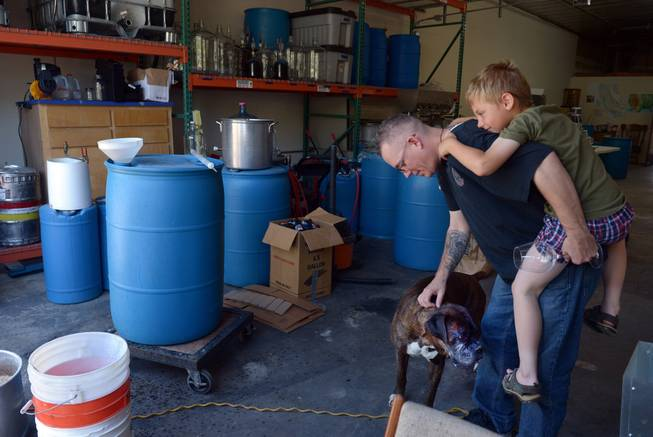 Marine Corps veteran Andy Kulakowski pets Socks at Uncle Sam's Misguided Brewery, with his son Mason Kulakowski hanging on in Livermore, Calif., on Monday, May 26, 2014. Free tastings were part of the brewery and winery's Memorial Day event for all veterans.