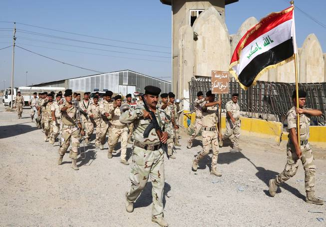 Iraqi army soldiers parade inside the main army recruiting center during a recruiting drive for men to volunteer for military service in Baghdad, Iraq, Thursday, June 19, 2014, after authorities urged Iraqis to help battle insurgents.