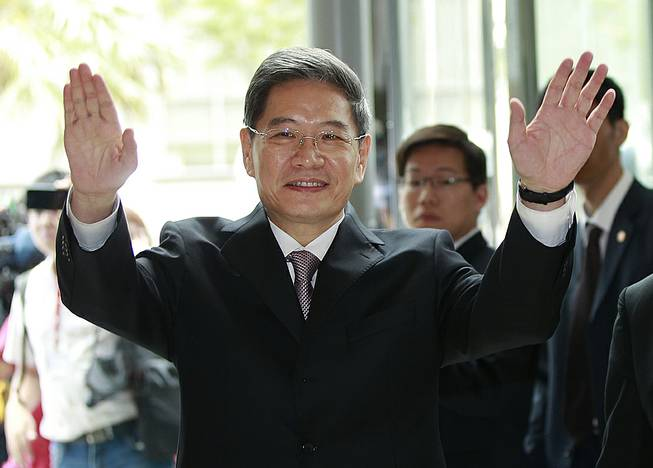 Zhang Zhijun, minister of Beijing's Taiwan Affairs Office, waves at the airport hotel upon arrival in Taoyuan, Taiwan, Wednesday, June 25, 2014.