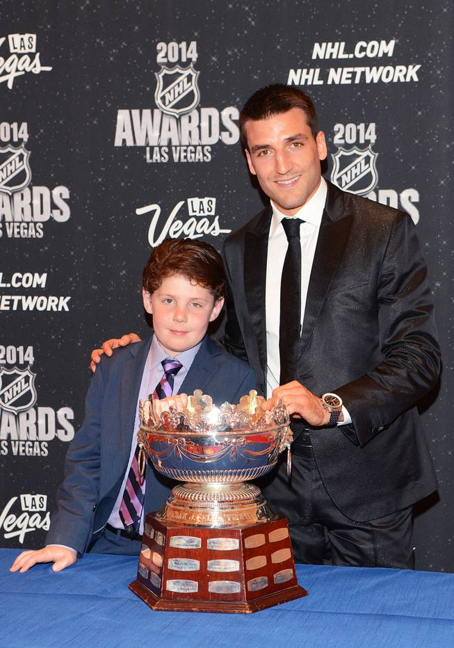 Nine-year-old Will Lacey of Boston, who is battling a brain tumor, with Patrice Bergeron of the Boston Bruins and the Frank J. Selke Trophy at the 2014 NHL Awards in Encore Theater on Tuesday, June 24, 2014, at Wynn Las Vegas.