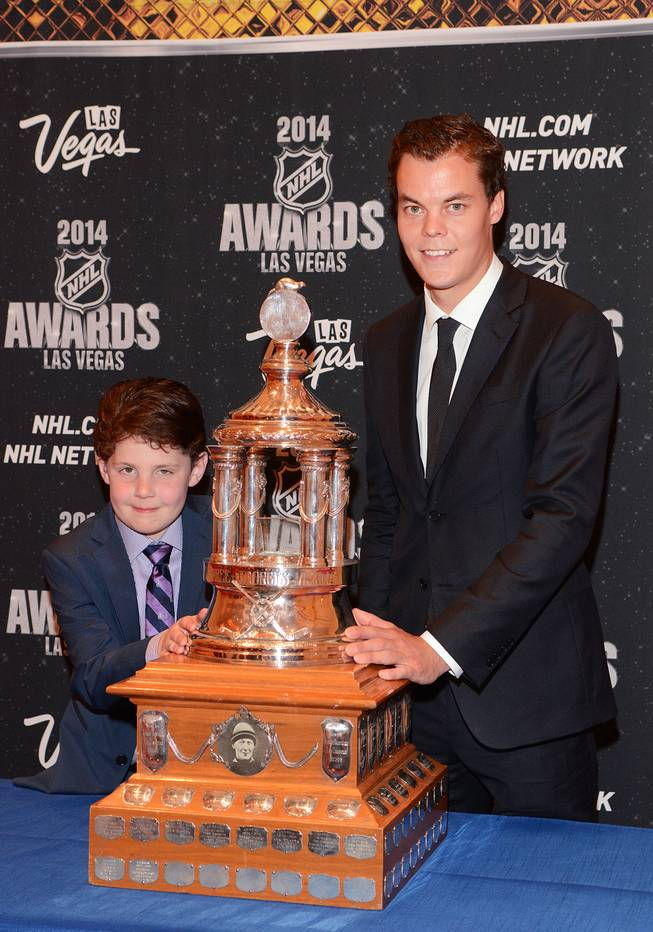 Nine-year-old Will Lacey of Boston, who is battling a brain tumor, and Tuukka Rask of the Boston Bruins with the Vezina Trophy at the 2014 NHL Awards in Encore Theater on Tuesday, June 24, 2014, at Wynn Las Vegas.