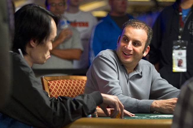 Poker player Abe Mosseri, right, talks with Macau's Chun Lei Zhou as they compete in the $50,000 World Series of Poker's Players' Championship at the Rio Wednesday, June 25, 2014.