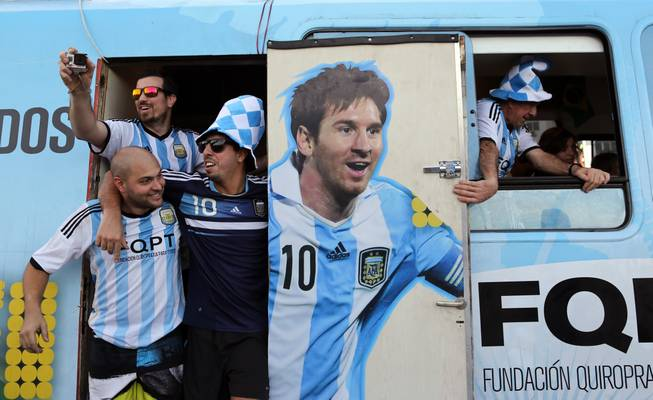 Argentine fans arrive in a bus decorated with a painting of soccer star Leonel Mesi at the Copacabana beach in Rio de Janeiro, Brazil,  Saturday June 14, 2014. Waving flags and banners, more than a thousand Argentine fans, many dressed in their team's traditional blue and white, crowded the Copacabana beachfront ahead of Argentina's World Cup match against Bosnia-Herzegovina Sunday in Rio's iconic Maracana stadium.