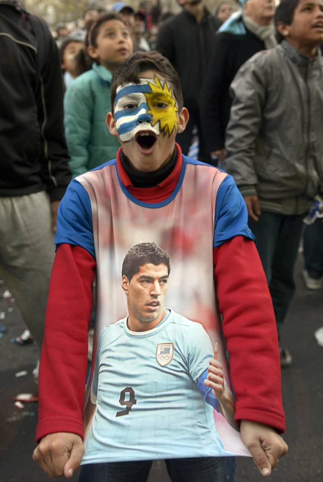 A soccer fan, with his face painted to represent his country's flag and wearing a T-shirt with an image of Uruguayan footballer Luis Suarez, cheers as he watches a live broadcast of the World Cup match between England and Uruguay in downtown Montevideo, Uruguay, Thursday, June 19, 2014. Suarez scored twice to give Uruguay a 2-1 victory over England, making an instant impact on his return from injury to revive his team's Group D campaign.