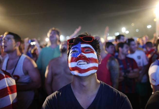 A soccer fan of the U.S. national soccer team watches a live broadcast of the soccer World Cup match between USA and Ghana, inside the FIFA Fan Fest area on Copacabana beach, Rio de Janeiro, Brazil, Monday, June 16, 2014.