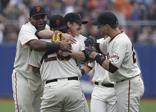 San Francisco Giants pitcher Tim Lincecum, center, is embraced by teammates, from left, Pablo Sandoval, catcher Hector Sanchez, and Buster Posey after throwing a no-hitter against the San Diego Padres, Wednesday, June 25, 2014, in San Francisco.