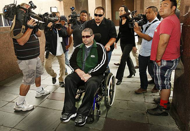 A wheelchair bound Bryan Stow, assisted by a caregiver, is surrounded by family and media as he is led into the Los Angeles County Superior Courthouse in downtown Los Angeles, Wednesday, June 25, 2014, as the trial goes into the last day before closing arguments for the trial of Stow's lawsuit against former Dodgers owner Frank McCourt and three team entities he created.