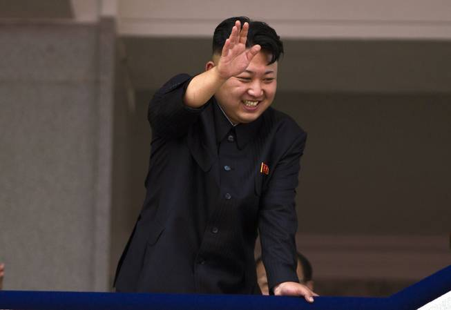 "In this July 27, 2013, file photo, North Korean leader Kim Jong Un leans over a balcony and waves to Korean War veterans cheering below at the end of a mass military parade on Kim Il Sung Square in Pyongyang to mark the 60th anniversary of the Korean War armistice. North Korea is warning that the release of a new American comedy about a plot to assassinate leader Kim Jong Un would be an ""act of war."""