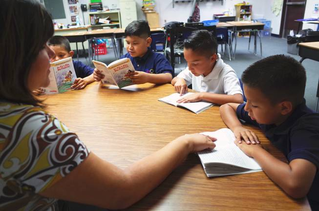 "Cortez Elementary School teacher Shasta Thompson reads with third graders (l-r) Isaiah Corona, 9; Uziel Umana, 9; Rafael Lucio, 9; and Reily Armenta, 8; on Monday, June 22, 2014. Cortez is one of 14 ""Zoom Schools"" in Clark County that is receiving 17 additional days of school this year to help English-language learner students retain their literacy skills over the summer."