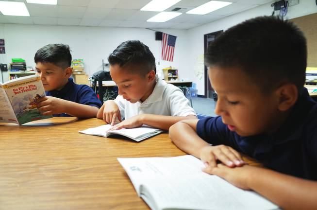 "Cortez Elementary School teacher Shasta Thompson reads with third graders (l-r) Uziel Umana, 9; Rafael Lucio, 9; and Reily Armenta, 8; on Monday, June 22, 2014. Cortez is one of 14 ""Zoom Schools"" in Clark County that is receiving 17 additional days of school this year to help English-language learner students retain their literacy skills over the summer."