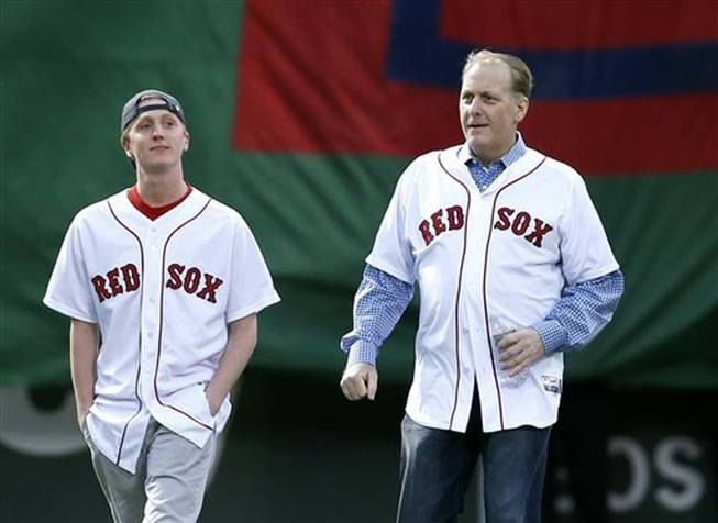 Former Boston Red Sox pitcher Curt Schilling, right, walks with his son, Garrett, onto the infield at Fenway Park prior to a baseball game against the Atlanta Braves in Boston on  Wednesday, May 28, 2014. The Red Sox honored the 2004 World Series team prior to the game.
