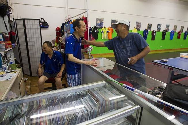 Jong Jin Lee, center, 73, talks with Percy Mariano about the price of paddles at the Nevada Table Tennis Center, 4063 Renate Dr. (Chinatown Mall), Wednesday, June 25, 2014. Sam Lee, left, 64, takes break to watch World Cup soccer on a television.