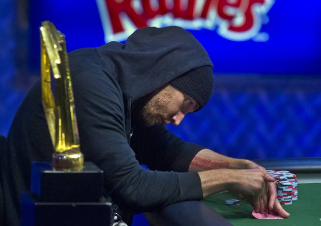 WSOP player Brandon Shack-Harris takes a peek at his cards during the Poker Players Championship final table of professional poker players at the Rio on Thursday, June 26, 2014.