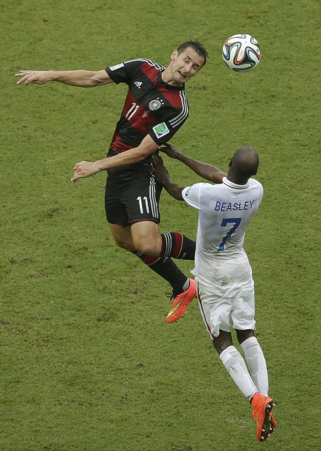 Germany's Miroslav Klose and United States' DaMarcus Beasley (7) go up for a header during the group G World Cup soccer match between the USA and Germany at the Arena Pernambuco in Recife, Brazil, Thursday, June 26, 2014.