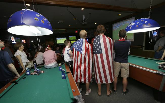 Fans draped in flags watch the World Cup Soccer match between the United States and Germany at a local bar, Thursday, June 26, 2014, in West Des Moines, Iowa.
