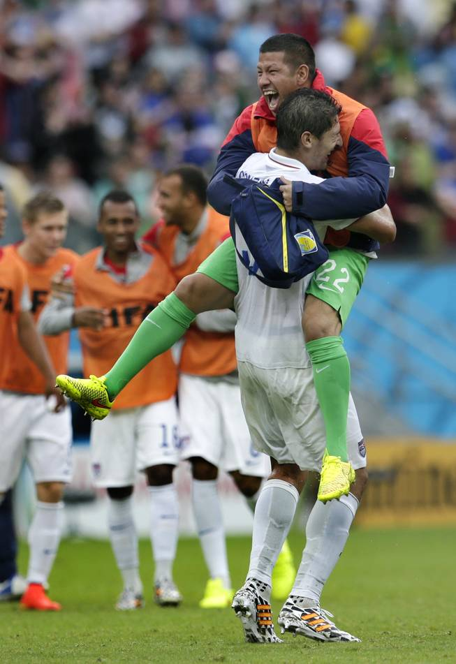 United States' goalkeeper Nick Rimando, right, celebrates with Omar Gonzalez after advancing to the round of 16 despite a 0-1 loss to Germany after the group G World Cup soccer match between the USA and Germany at the Arena Pernambuco in Recife, Brazil, Thursday, June 26, 2014.