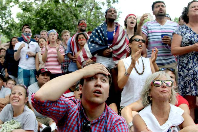 Jack Cooper, 24, center, of Washington, and others, react while watching the US-Germany World Cup soccer match, Thursday, June 26 2014, during a viewing party sponsored by the German Embassy at Dupont Circle in Washington.