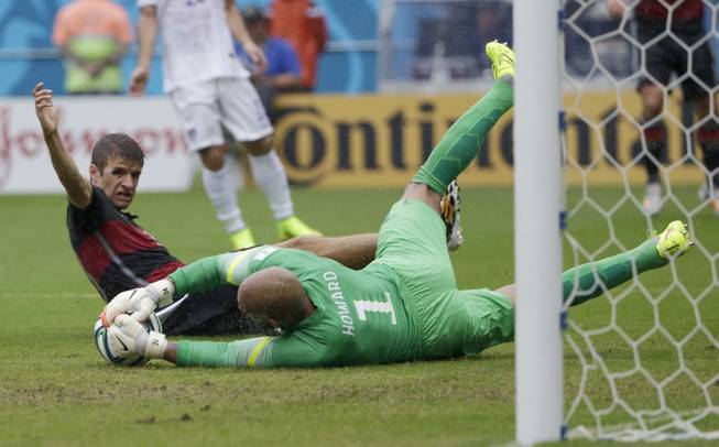 United States' goalkeeper Tim Howard dives to make a save on Germany's Thomas Mueller during the group G World Cup soccer match between the USA and Germany at the Arena Pernambuco in Recife, Brazil, Thursday, June 26, 2014.