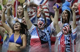 US fans celebrate after their team advanced to the round of 16 despite losing 0-1 to Germany during the group G World Cup soccer match between the USA and Germany at the Arena Pernambuco in Recife, Brazil, Thursday, June 26, 2014.