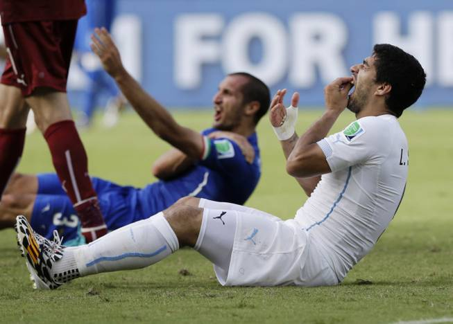 In this June 24, 2014, file photo, Uruguay's Luis Suarez holds his teeth after biting Italy's Giorgio Chiellini's shoulder during the group D World Cup soccer match between Italy and Uruguay at the Arena das Dunas in Natal, Brazil. On Thursday, June 26, 2014, FIFA banned Suarez for 9 games and 4 months for biting his opponent at the World Cup.