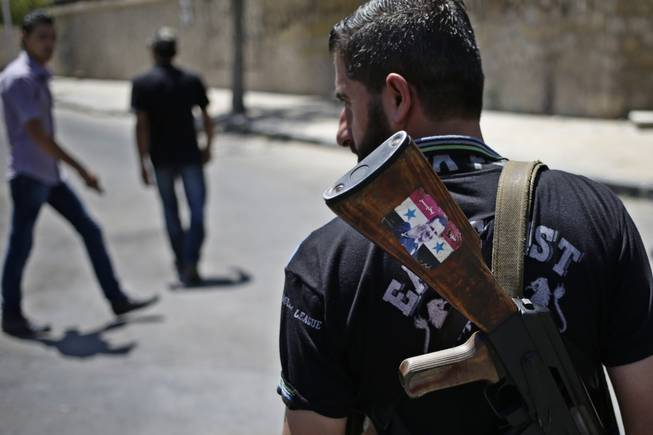 "This Aug. 21, 2013, file photo shows a Syrian military soldier holding his AK-47 with a sticker of Syrian President Bashar Assad and Arabic that reads, ""Syria is fine,"" as he stands guard at a check point in Damascus, Syria. President Barack Obama is asking Congress for $500 million to train and arm vetted members of the Syrian opposition, as the U.S. grapples for a way to stem a civil war that has also fueled the al-Qaida inspired insurgency in neighboring Iraq."