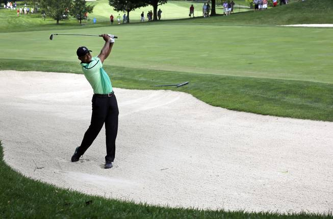 Tiger Woods chips out of a sand trap on the ninth fairway during the first round of the Quicken Loans National PGA golf tournament, Thursday, June 26, 2014, in Bethesda, Md.