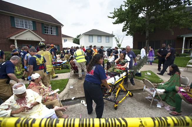 Firefighters and emergency crews treated people outside in a makeshift triage area set up in the front yards of nearby homes after a floor collapsed under a large crowd of people gathered for a religious event Thursday, June 26, 2014, in Katy, Texas.