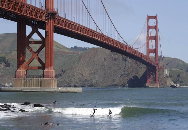 Two surfers ride a wave near Fort Point below the Golden Gate Bridge in this May 3, 2014, file photo in San Francisco.