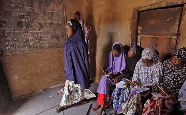 Maimuna Abdullahi, left, moves toward the blackboard during class as she and others attend school in Kaduna, Nigeria, Monday, June 2, 2014.