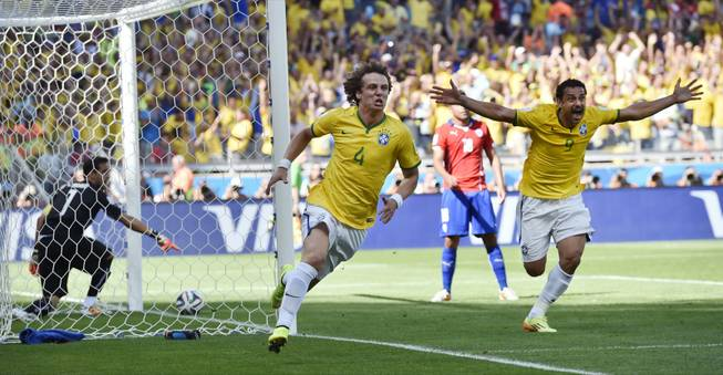 Brazil's David Luiz, left, and Fred celebrate after Brazil's opening goal during the World Cup round of 16 soccer match against Chile at the Mineirao Stadium in Belo Horizonte, Brazil, on Saturday, June 28, 2014.