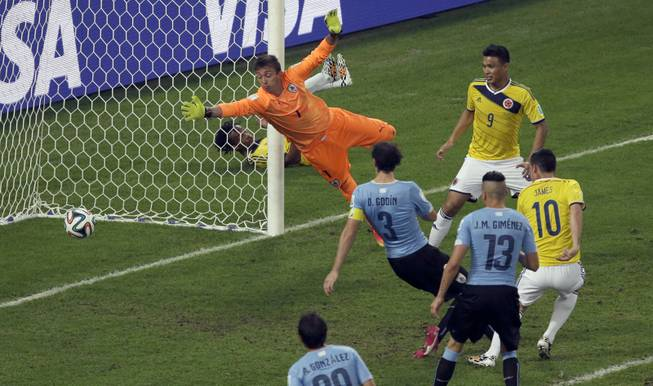 Colombia's James Rodriguez, right, scores his side's second goal past Uruguay goalkeeper Fernando Muslera during a World Cup round of 16 soccer match at the Maracana Stadium in Rio de Janeiro, Brazil, on Saturday, June 28, 2014.