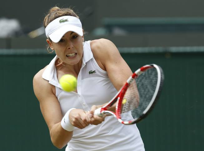 Alize Cornet of France hits a return to Serena Williams of U.S. during their women's singles match at the All England Lawn Tennis Championships on Saturday, June 28, 2014.