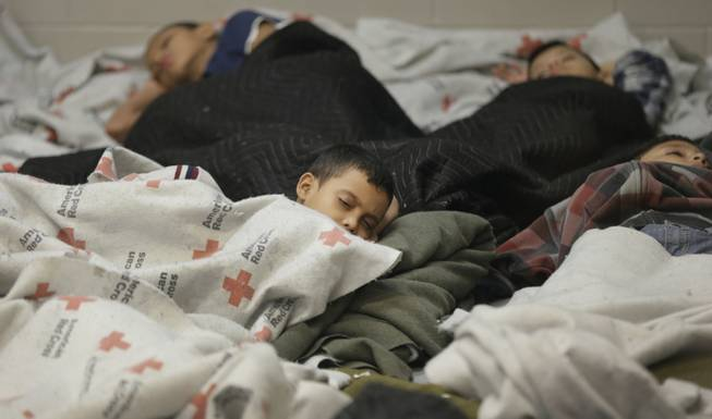 This June 18, 2014, file photo shows children detainees sleeping in a holding cell at a U.S. Customs and Border Protection processing facility in Brownsville, Texas.